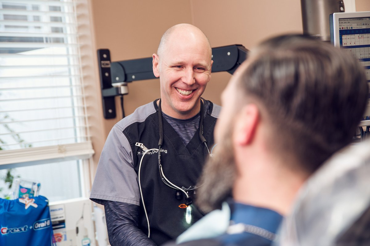 Dentist, Dr. Durling, smiling while talking to patient at the dental office.