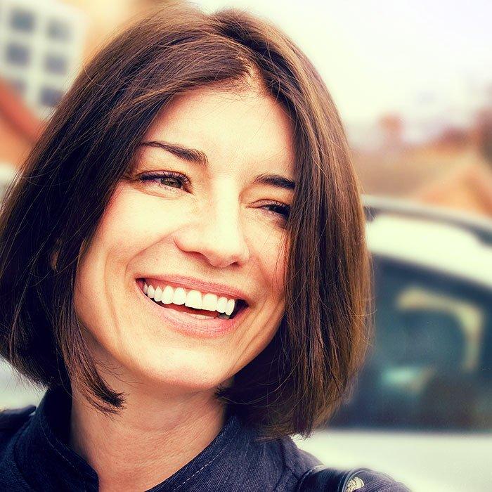 Brunet woman smiling outside of dental office.