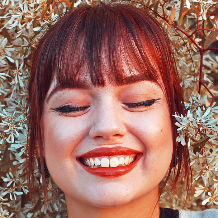 Redhead woman smiling with eyes closed outside dentist office.