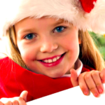 Little girl smiling wearing a santa hat at the dentist.