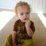 White toddler boy brushing his teeth.