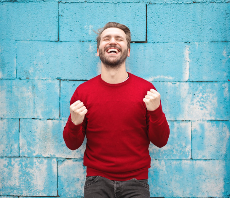 Blonde man smiling and happy with clear aligners.