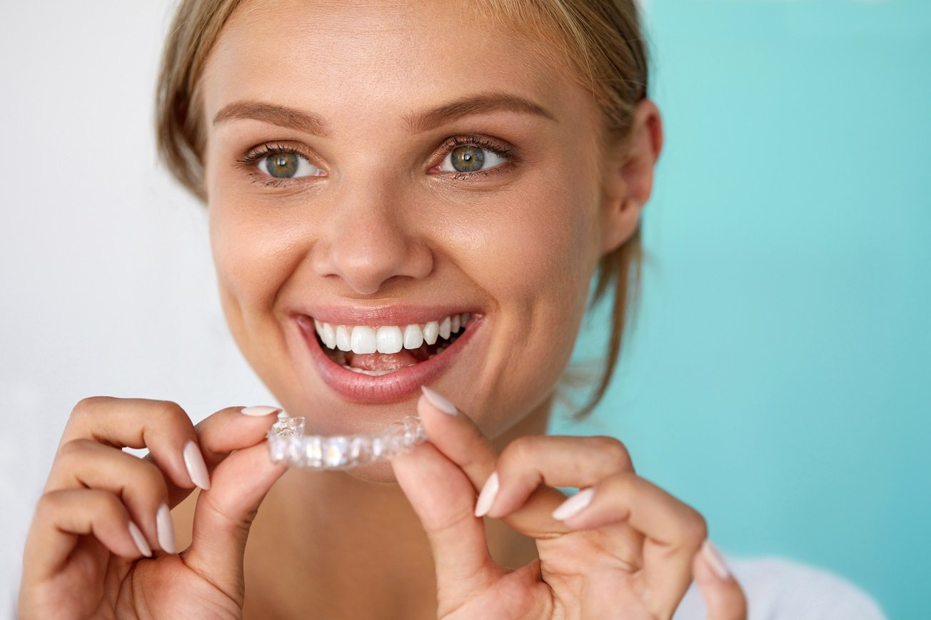 Blonde woman smiling about to put on her clear aligners.