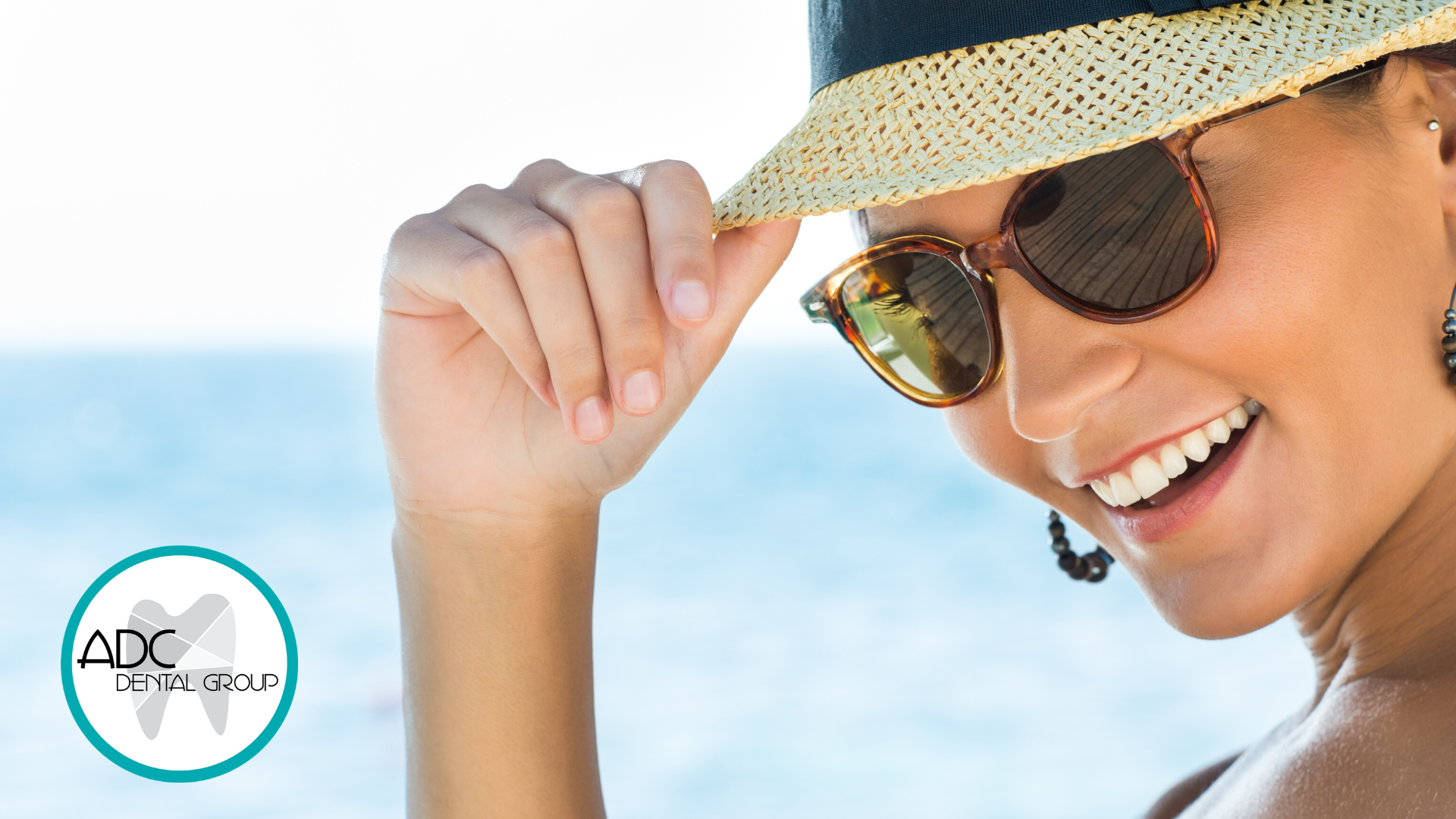 Woman wearing a hat and sunglasses smiling outside.