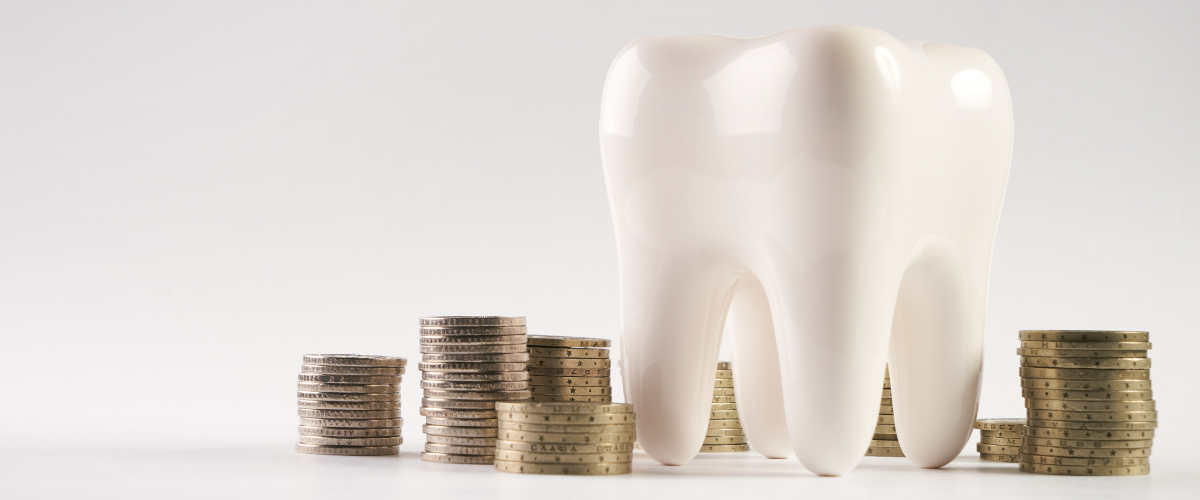 A white tooth next to stacks of coins to indicate an affordable dentist in Joplin, MO